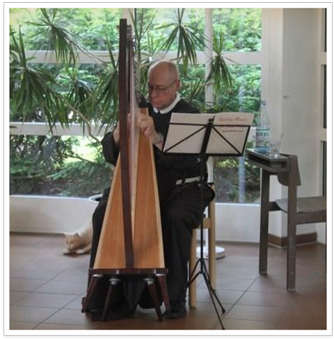 Picture of a Franciscan Brother playing the harp